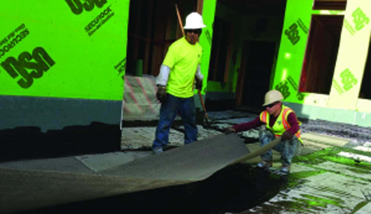 Construction workers installing a water proofing system
