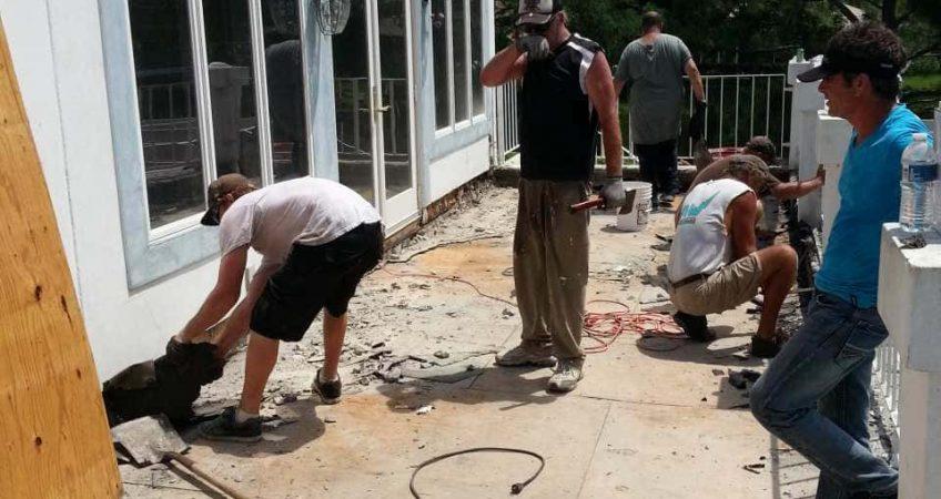 Workers on job site repairing plywood decking