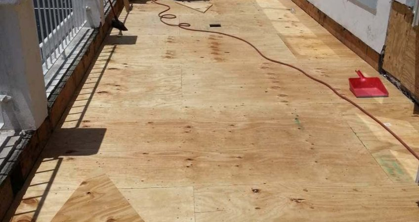 an installer prepping plywood for a waterproofing system