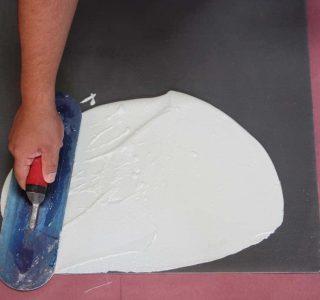 Worker applying Pli-Dek waterproofing solution with hand trowel