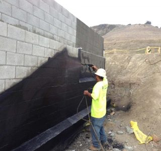 Below Grade Waterproofing: Construction Worker spraying wall