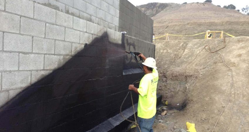 Below Grade Waterproofing: Construction Worker spraying wall